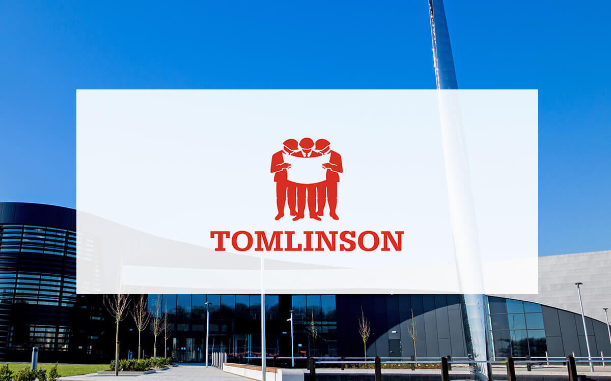 G F Tomlinson logo on white background with building in background
